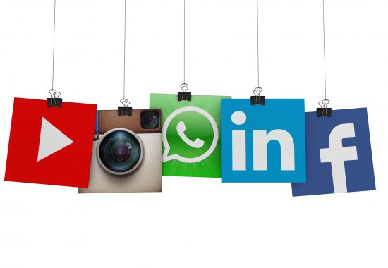 London, United Kingdom- March 15, 2016: Social media  and technology logos printed onto paper hanging on strings. Logos include Facebook, instagram, linkedin and whats app. Social media uses web and mobile technology to connect people